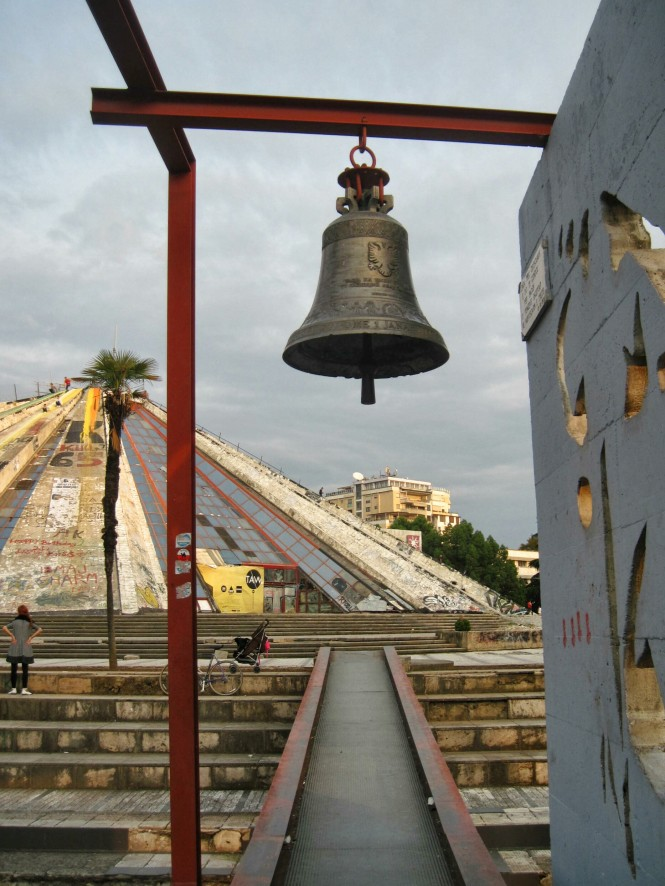 "The ""Bell of Peace,"" situated in front of the Hoxha pyramid, was cast from discarded shell casings from the 1997 turmoil"