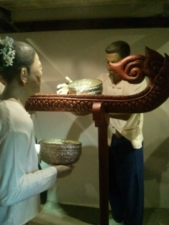 Mannequins demonstrate the special tool used to bathe the Buddha image as an offering