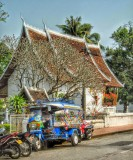 brightly colored tuk tuk in front of a temple
