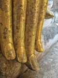 The Lanna-style tapered fingers are covered in gold leaf