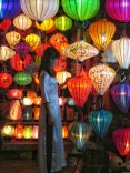 A woman in a traditional ao dai getting formal pictures done in a lantern store