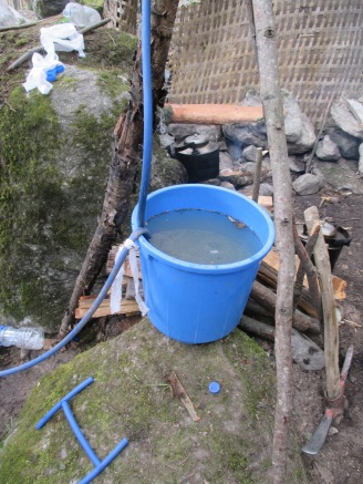 The bucket of cold river water that the hose coiled inside