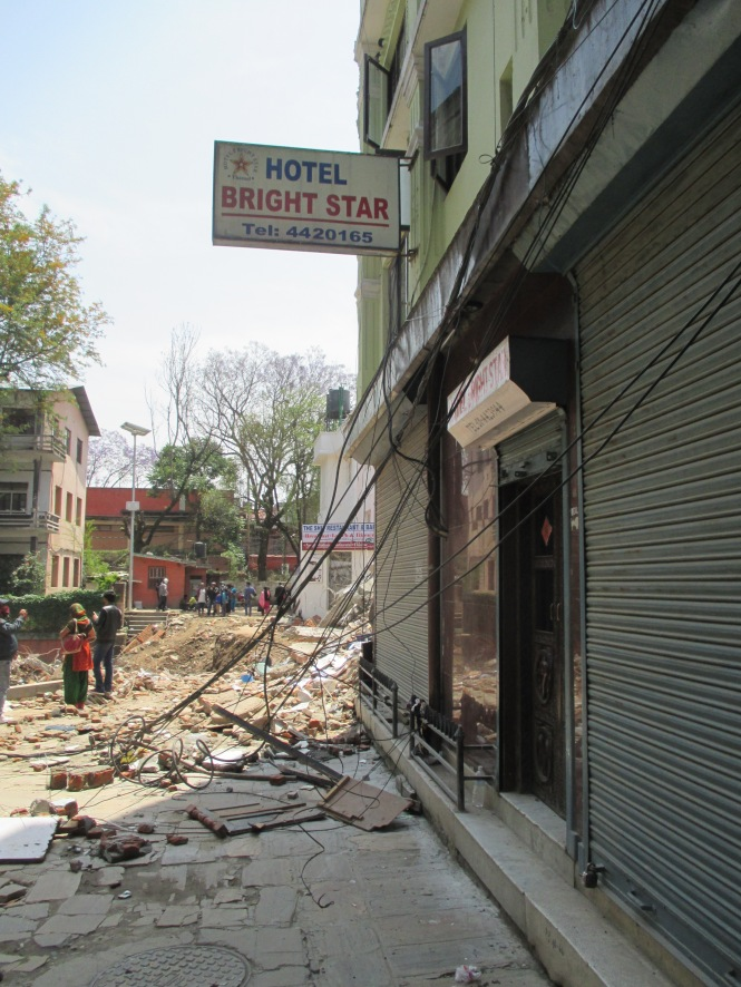 The same view after the quake, with the hotel just beyond in rubble